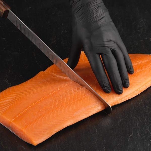 Filet knife cutting side of smoked salmon